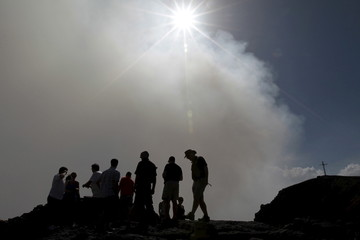 Tourists observe the main crater of the Santiago volcano during their visit to Masaya National Park