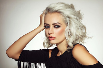 Vintage style portrait of young beautiful platinum blond woman with smoky eyes make-up