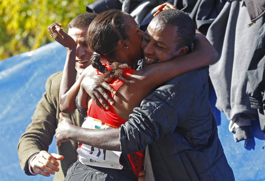 Firehiwot Dado of Ethiopia celebrates with family and friends after winning the women's division of the 2011 New York City Marathon in New York,