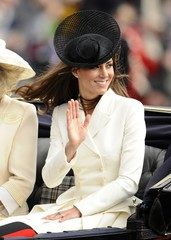 Britain's Catherine, Duchess of Cambridge waves to the crowd as she sits in a horse drawn carriage with other members of the royal family as they make their way to Buckingham Palace after attending the Trooping the Colour ceremony in central London