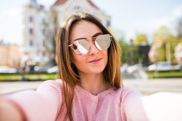 Young woman taking selfie from hands with mobile phone in sunny city street.