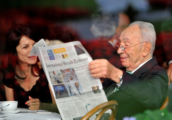 File photo of Israeli President Shimon Peres reading a newspaper during the Ambrosetti workshop in Cernobbio