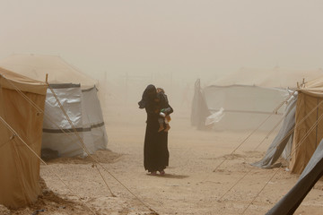 A woman carries her child during a dust storm at a refugee camp in Ameriyat Falluja