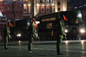 Servicemen take part in a rehearsal for the annual Victory Day parade, with Russian missile launchers Topol-M moving past in the background, in Red Square in Moscow