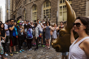 Tourists pose for photographs with a landmark statue of a bull in New York