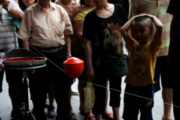 A spinning top spins on a fishing line during a performance at Sanxia old street in New Taipei City