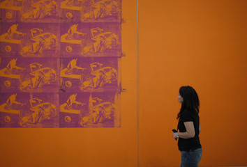 A woman looks at Andy Warhol's silkscreen painting 'Orange Car Crash' during a preview of the exhibition 'Museum of wishes' at MUMOK (Museum of modern art) in Vienna