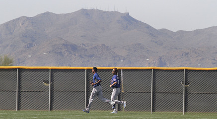 Rangers' rookie pitcher Yu Darvish of Japan runs wind sprints with the White Tank Mountains in the background during spring training in Surprise