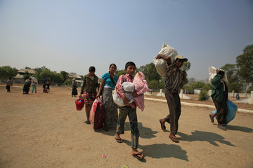 Muslims carry their belongings as they arrive at a stadium amid riots in Meikhtila