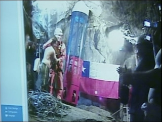 Video grab of rescue worker Manuel Gonzalez being welcomed by trapped miners as his rescue capsule reaches down to hoist trapped miners out at San Jose mine in Copiapo