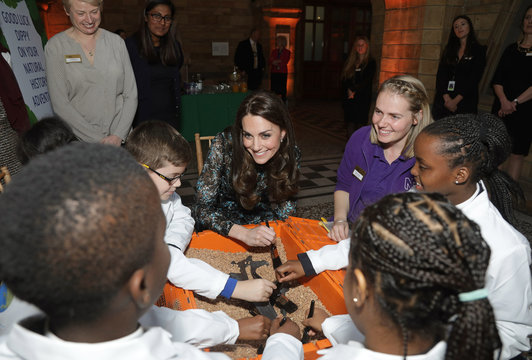Britain's Catherine, Duchess of Cambridge examines a replica Diplodocus fossil as she attends a children's tea party, to celebrate Dippy the Diplodocus's time in Hintze Hall, at the Natural History Museum in London