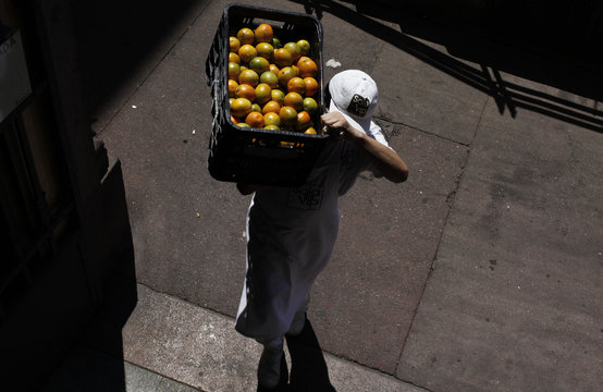 Worker carries a box of oranges at the Municipal Market in Sao Paulo
