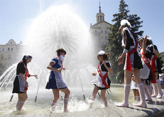 Secondary school graduates dressed in traditional uniforms play in a fountain as they celebrate the last day of school in Kiev