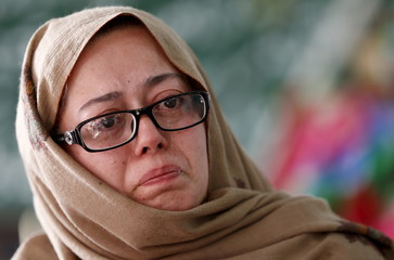 Gul E Rana, mother of Mohammad Ali Khan, cries as she describes her son in the rooftop shrine for Hassan Zeb in Peshawar