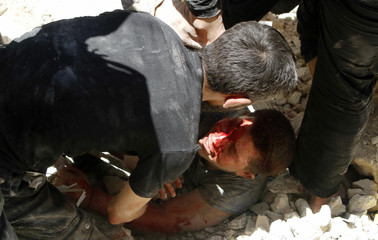 A man tries to pull an injured man from under the rubble of collapsed buildings at a site hit by what activists said was a barrel bomb dropped by forces loyal to Syria's President al-Assad in Aleppo