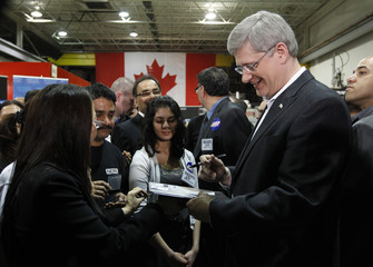 Conservative leader and Canada's PM Harper signs autographs during a campaign stop at a plastics factory in Markham