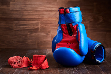 Pair of red and blue boxing gloves and red bandage on brown plank.