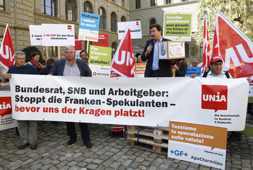 Swiss inter-professional trade union UNIA member and National Councillor Pardini holds up a box of a petition to the Swiss Federal Council against the speculation with the strong Swiss franc in Bern