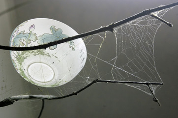 A ceramic bowl, made by ceramic artist Huang Cheng-nan, rests on a cobweb in Taipei county