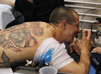 Ron Raucci reacts to the needle while getting his Captain America tattoo at the Hampton Roads Tattoo Festival in Virginia