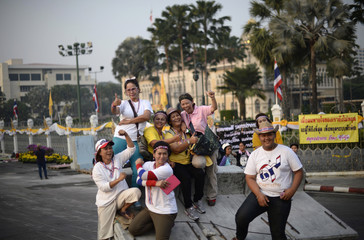 Anti-government protesters pose for pictures after waking up outside Government House in Bangkok