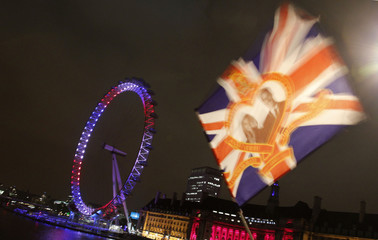 A flag showing a picture of Britain's Prince William and his fiancee Kate Middleton flutters in the wind as a passer-by crosses the bridge next to the illuminated London Eye in London late evening