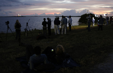 News photographers and journalists watch as the sun rises on the Delta IV Heavy rocket carrying the Orion spacecraft waiting for liftoff  on the launch pad from the Cape Canveral Air Force Station in Cape Canavera