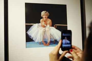 A woman takes picture of a framed Marilyn Monroe photo at gallery in Warsaw