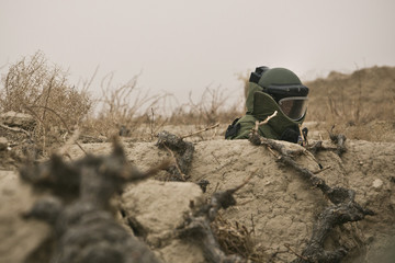 A member of a U.S. Army EOD team patrols a patch of farm land during a mission near Command Outpost AJK (short for Azim-Jan-Kariz, a near-by village) in Maiwand District, Kandahar Province