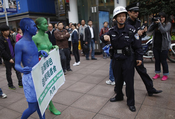 """Two PETA members painted in blue and green, are stopped by police after marching with a banner that reads """"Save the Planet, Go Vegan"""", along a pedestrian area of Nanjing Road in downtown Shanghai"""