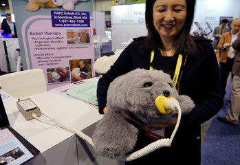 Christine Hsu shows off the Paro seal pup therapeutic robot at the Robotics Marketplace at CES in Las Vegas