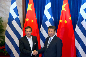 Greek Prime Minister Alexis Tsipras shakes hands with Chinese President Xi Jinping during a meeting at the Great Hall of the People in Beijing