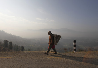 A woman carries a basket on her back as she heads toward a field at Changunarayan in Bhaktapur