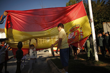 Children hoist the Spanish flag with Spanish legionnaires during an flag-honouring ceremony on the eve of the Spain's National Day in downtown Ronda
