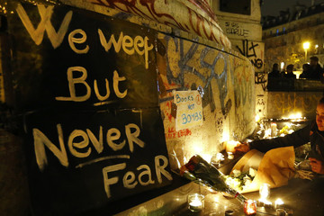 Flowers and candles are placed near the scene of a shooting the day after a series of deadly attacks in Paris