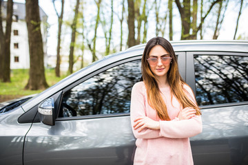 Young woman standing next to her new car in city street