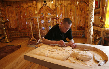 An inmate carves a wooden icon inside a Orthodox church at a high-security camp for male prisoners in Ariysk village, outside the Siberian city of Krasnoyarsk, Russia