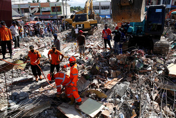 Rescue teams use heavy equipment to dig through a collapsed building following a strong earthquake in Meureudu market, Pidie Jaya, Aceh province