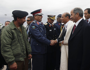 Tunisia's President Marzouki shakes hands with Libyan officials upon arriving at Tripoli International Airport