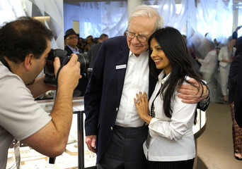 Berkshire Hathaway CEO Warren Buffett poses for a picture with Tinku Jain, wife of Ajit Jain, who runs Berkshire's giant reinsurance division at the Berkshire-owned Borsheims jewelry store where Buffett was selling jewelry as part of the company annual mee