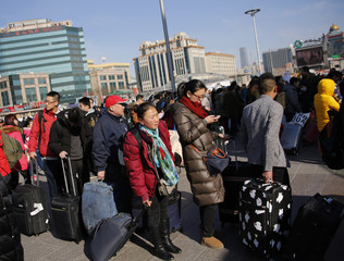 Passengers stand in a line to pick up their tickets in front of the Beijing Railway StatioN during the travel rush ahead of the upcoming Spring Festival in Beijing
