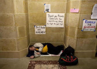 A man sleeps as his fellow demonstrators continue to occupy the state Capitol in protest against proposed budget cuts in Madison