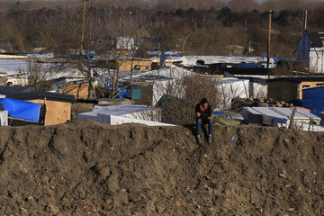 """A migrant sits on top of a pile of sand which separates the road that leads to the ferry terminal and the camp known as the """"Jungle"""", a squalid sprawling camp in Calais"""