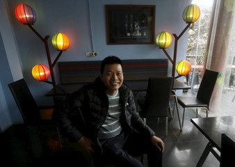 Tran Khanh Sinh, a gay person, poses for a photo in front of lamps in the colours of the gay rainbow flag at Comga restaurant where he is working in Hanoi