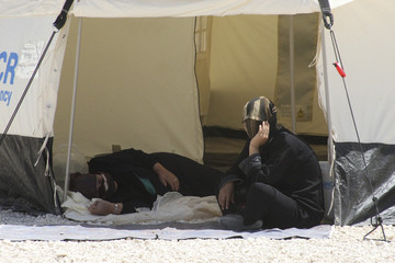 Syrian refugees look out from their tent at the Za'atri refugee camp in the Jordanian city of Mafraq