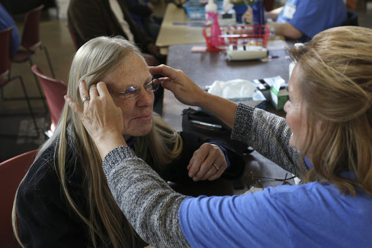 Optician Ginny Mercer helps Kanti Kish select a pair of free eyeglasses during the Seattle/King County Clinic, a four-day event offering free dental, vision, and medical care, at Key Arena in Seattle, Washington