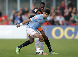 Celta Vigo's Augusto fights for the ball with Valencia's Aly Cissokho during their Spanish first division soccer match in Vigo