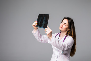 Female doctor examining an x-ray image. Focus is on the x-ray image isolated on grey background.