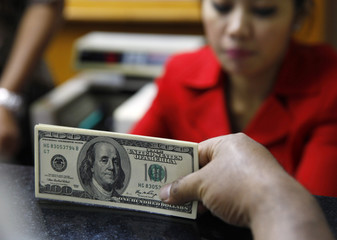 A money changer holds a stack of U.S. dollar notes in Jakarta