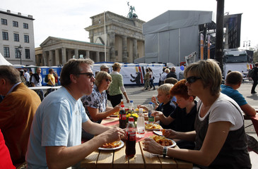 People eat their lunch near the Brandenburg Gate during German reunification celebrations in Berlin
